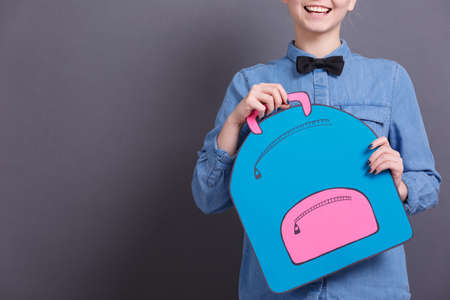 A young girl in a blue shirt with a big paper backpack on a gray blackboard. School objects concept