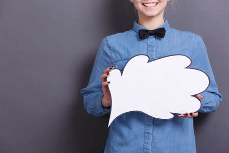 The young businesswoman with smile holds white paper cloud on a gray background. A woman with business ideas and thoughts concept.