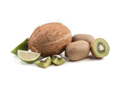 Sliced on halves and whole ripe kiwis, lime and a whole coconut isolated on a white background. A concept of exotic fruits full of vitamins