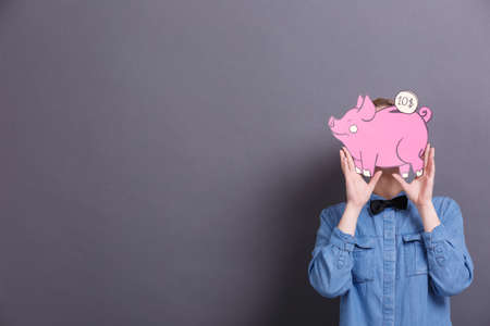 A young woman holds a big paper pink piggy bank with a coin on a gray background. The concept of money and finance Banco de Imagens
