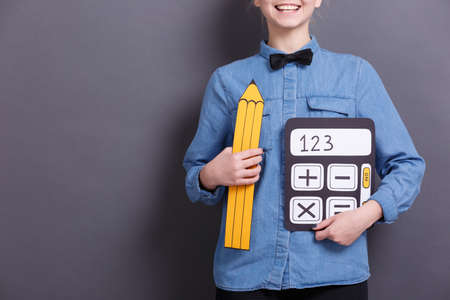 A young woman holds an image of a yellow pencil and a calculator on a gray background. Objects for work with documents. 스톡 콘텐츠