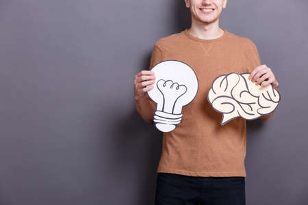 A young man holds paper brain and lamp bulb on a gray background. Concept of ideas 스톡 콘텐츠