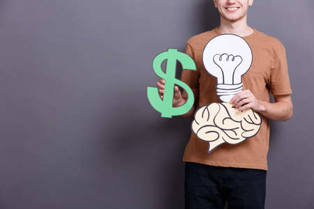 A young man holds an American green big dollar, paper brain and lamp bulb on a gray background. Concept of money