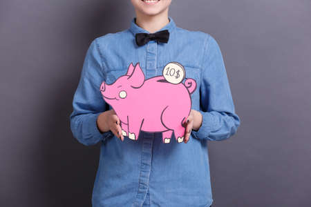 A young woman holds a big paper pink piggy bank with a coin on a gray background. The concept of money and finance 스톡 콘텐츠