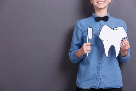 A young woman in blue shirt holds a paper image of a big paper tooth and a toothbrush on a gray background. Healthcare concept.