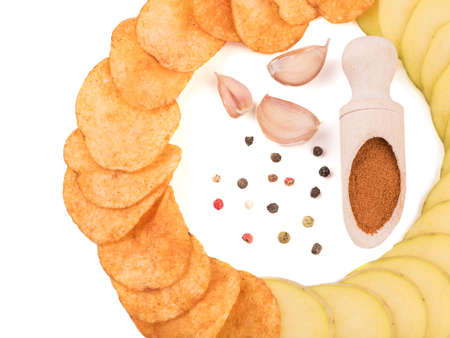 Crispy potato chips with spices from pepper isolated on a white background. Junk food concept. Close-up of a fast snack.