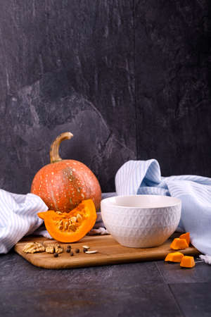 Close-up of Halloween pumpkin with a plate of gourd soup on a gray background. The concept of autumn holidays and seasonal harvest 스톡 콘텐츠