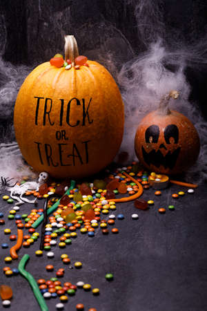 Halloween pumpkin with sweet candies on a dark background. The concept of autumn holidays, close-up. Lettering trick and treat on a gourd.