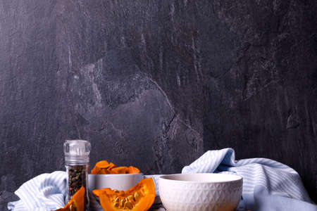 Halloween pumpkin with a plate of gourd soup on a dark background. The concept of autumn holidays and seasonal harvest, close-up