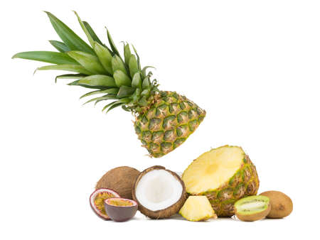A sliced ripe and tropical pineapple, juicy passion fruit, kiwi and halved coconut pieces isolated on a white background.