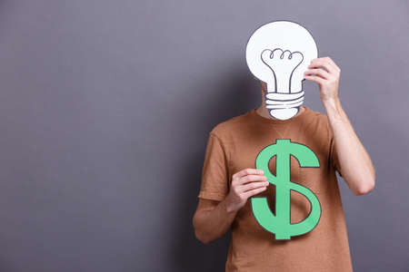 A young man holds an American green big dollar, paper lamp bulb on a gray background. Concept of money 스톡 콘텐츠