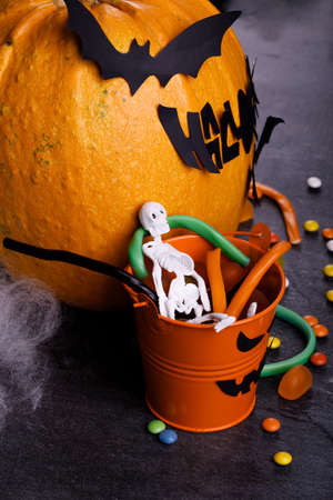 Halloween pumpkin with candles, spiders, web, sweets, horror stories on a dark background, closeup. The concept of autumn holidays. 스톡 콘텐츠