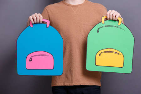 A young guy holding two colorful paper backpack on a gray background. The concept of education and school objects