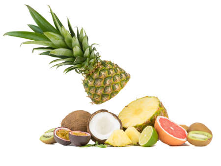 A sliced ripe and tropical pineapple, juicy passion fruit, grapefruit, kiwi and halved coconut pieces isolated on a white background.