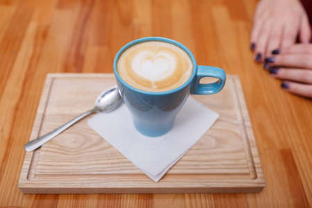 A cup of cappuccino coffee on a light brown wooden table in cafe. Women's hands with hot drink