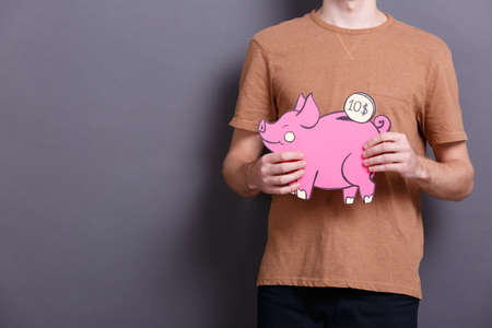 A young man holds a big paper pink piggy bank with a coin on a gray background. The concept of money and finance
