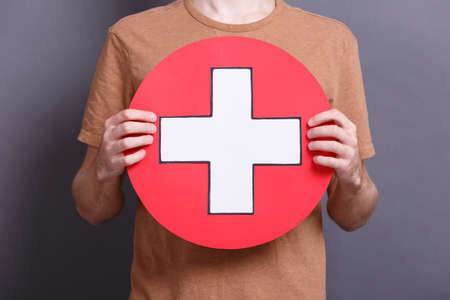 A young man with a big paper edical cross icon on a gray blackboard. School objects concept