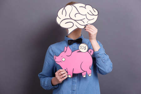 A young woman holds a big paper pink piggy bank with a coin and a big brain on a gray background. The concept of money and finance