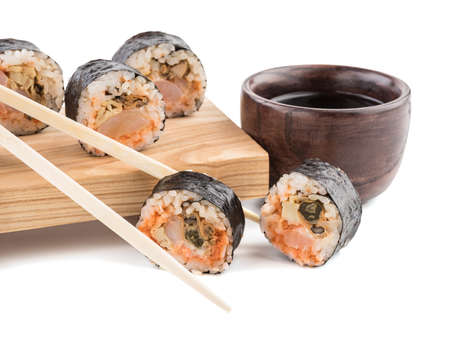 A set of sushi rolls with chopsticks and soy sauce on a wooden board isolated on white background. A concept of seafood and Japanese cuisine.