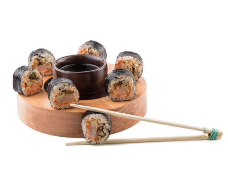A set of sushi rolls with chopsticks and soy sauce on a round wooden board isolated on white background. A concept of seafood and Japanese cuisine. Stock Photo