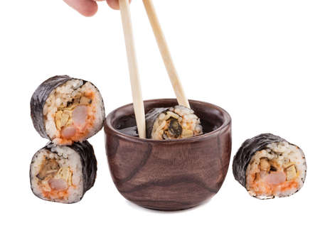 A set of sushi rolls with chopsticks and soy sauce isolated on white background. A concept of seafood and Japanese cuisine. 스톡 콘텐츠
