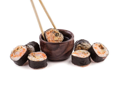 A set of sushi rolls with chopsticks and soy sauce isolated on white background. A concept of seafood and Japanese cuisine. Banco de Imagens