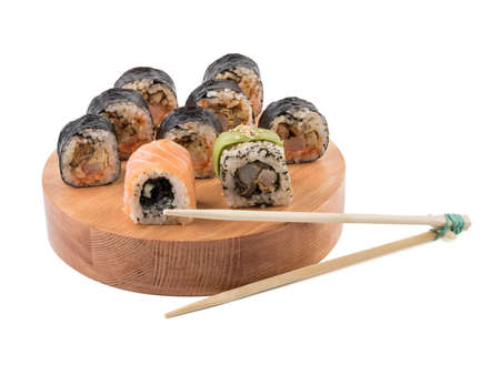 A set of sushi rolls with chopsticks on a round wooden board isolated on white background. A concept of seafood and Japanese cuisine. Banco de Imagens