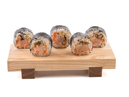 A set of sushi rolls on a wooden board isolated on white background. A concept of seafood and Japanese cuisine. Banco de Imagens