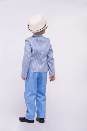 A back of little boy in an elegant suit and a hat on a white background. Happy children concept Reklamní fotografie