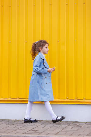 A cute little girl in a blue denim coat on a bright yellow background outdoors. Fall fashion clothes for kids concept.