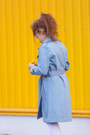 A cute little girl in a blue denim coat on a bright yellow background. Fall fashion clothes for kids concept.