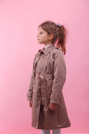 Portrait of a smiling little girl in an autumn coat on a pink background. Childrens autumn clothes concept.