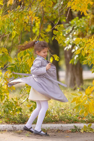 A cute little girl in an autumn coat running and having fun in the park. Autumn concept. Standard-Bild - 111015865