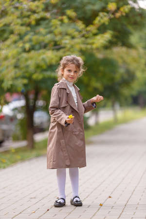 A pretty little girl in an autumn coat in the park. Autumn concept.