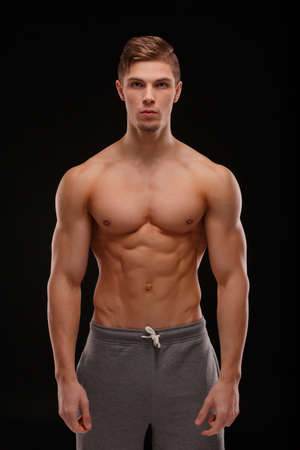 A sexy sportsman with perfect muscles on a black background. Gym, workout, exercising concept