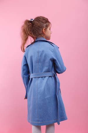 A back of a little girl in a blue denim coat on a pink background. Fall and spring fashion concept.