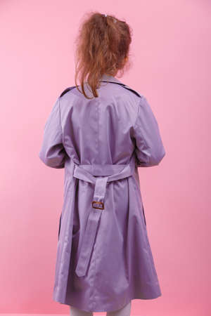 A back of a little girl in a purple coat on a pink background. Fall and spring fashion concept.
