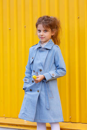 A beautiful little girl in a blue denim coat on a bright yellow background. Fall fashion clothes for kids concept.