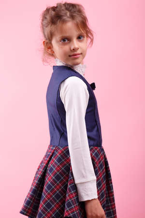 A cute little girl in a school uniform on a pink background. Education, school concept Banco de Imagens