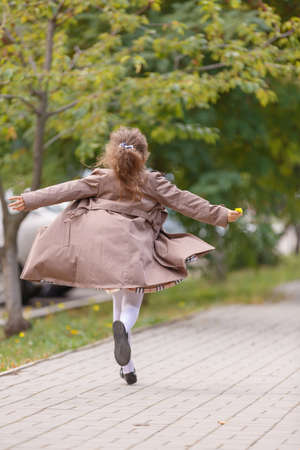 A happy little girl in an autumn coat running and having fun in the park. Autumn concept.
