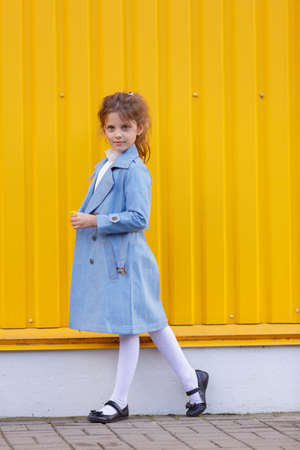 A pretty little girl in a blue denim coat on a bright yellow background. Fall fashion clothes for kids concept.