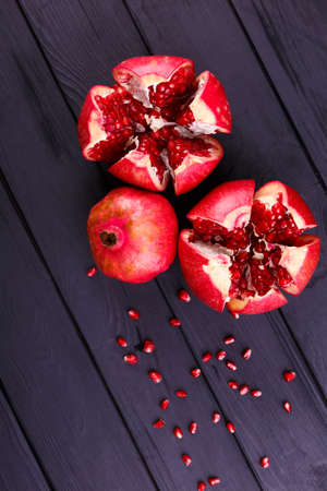 The sweet, fresh and natural garnet for desserts and beverages on a black background. Bright red pomegranate broke down into parts Standard-Bild - 111051419