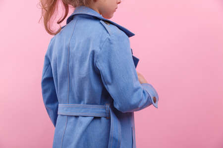 A back of a schooler girl in a blue denim coat on a bright pink background, close-up. Fall and spring children's fashion concept.