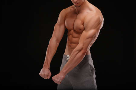 A body of a sexy sportsman with naked muscular torso on a black background. Strong and powerful concept.