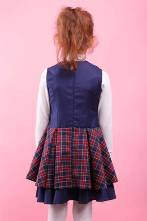 A back of girl in a school uniform on a bright pink background, close-up. Education, school concept. Reklamní fotografie