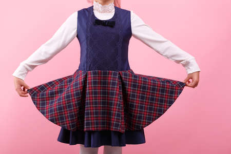 A body of little girl in a school uniform on a bright pink background, close-up. Education, school concept. 스톡 콘텐츠 - 111051435