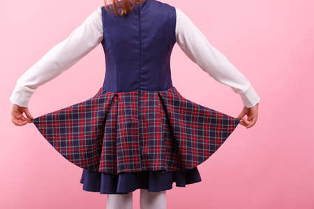 A back of girl in a school uniform on a bright pink background, close-up. Education, school concept. Banco de Imagens