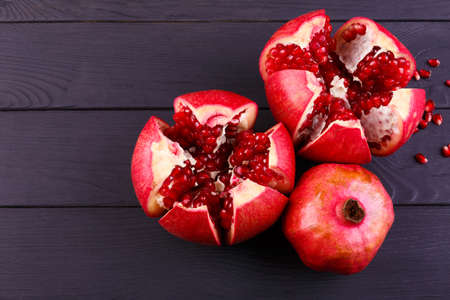 The sweet, fresh and natural garnet for desserts and beverages on a black background. Bright red pomegranate broke down into parts Stock Photo