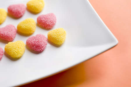 scattered in heart shaped: Heart shaped gummy candy, orange background, valentine s day  Stock Photo