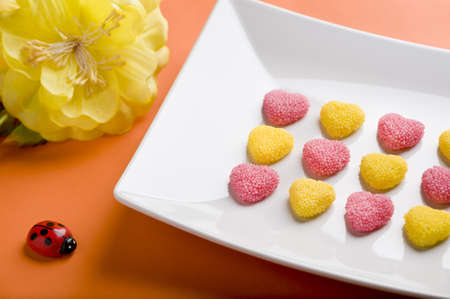 scattered in heart shaped: Heart Valentine s candy with ladybug, flower, orange background